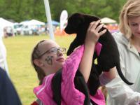 girl hold puppy high